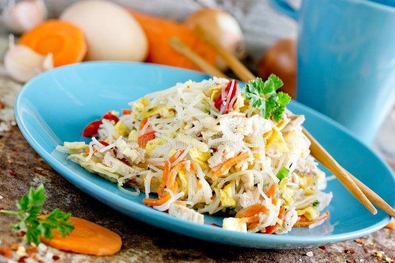 Rice noodles with fried eggs, chicken and vegetables stock photo