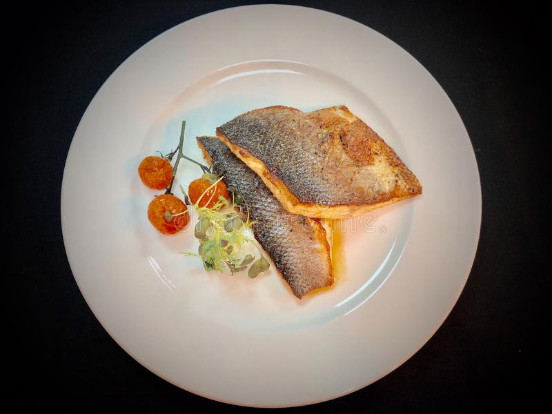 Pan fried sea bass fish fillet in a plate with black background stock photography