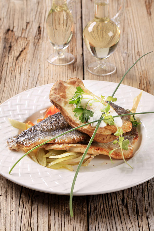 Pan fried trout and baked potato stock photography