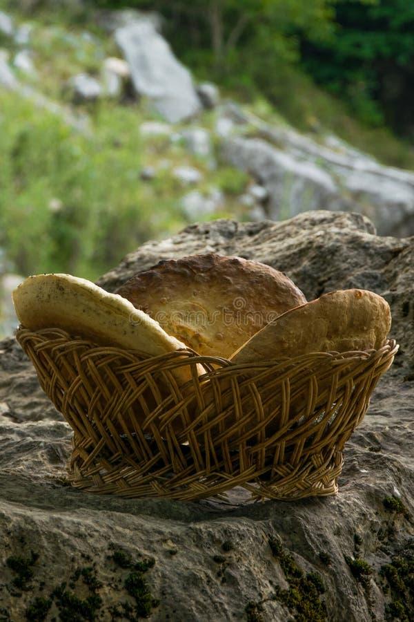 Pan hecho en casa ácimo tradicional en cesta de madera en la roca foto de archivo libre de regalías