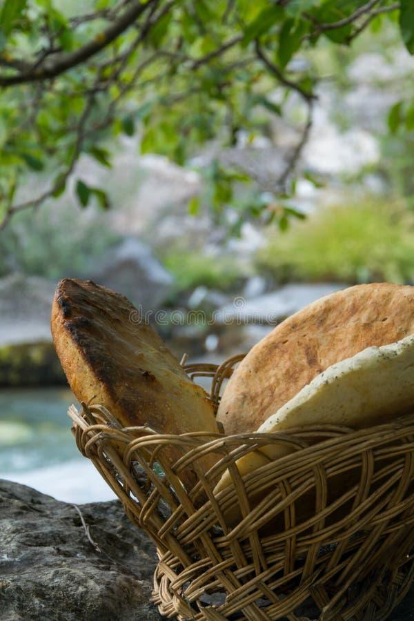 Pan hecho en casa ácimo tradicional en cesta de madera en la roca imagen de archivo