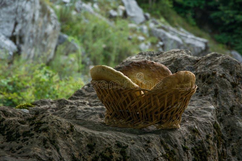 Pan hecho en casa ácimo tradicional en cesta de madera en la roca imagenes de archivo