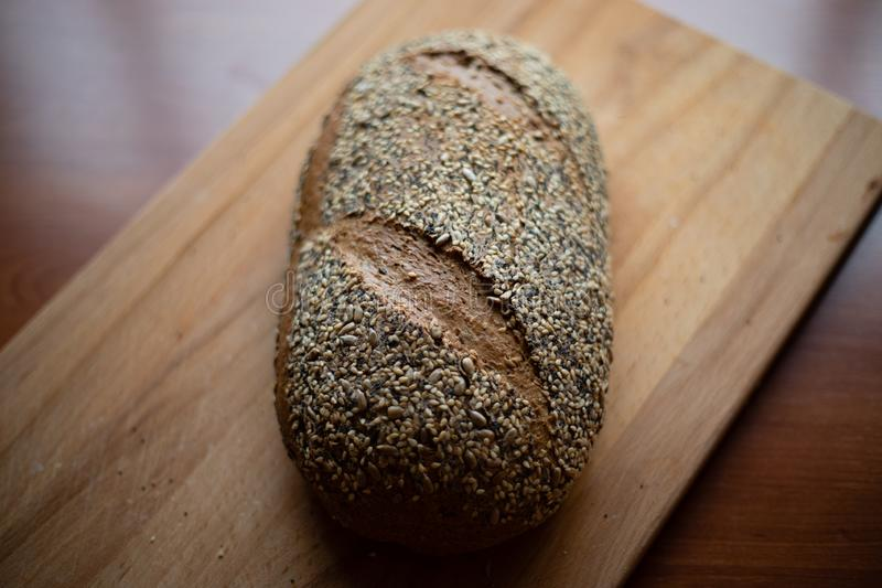 Pan hecho en casa de Multigrain en una tabla de cortar de madera en casa fotografía de archivo libre de regalías