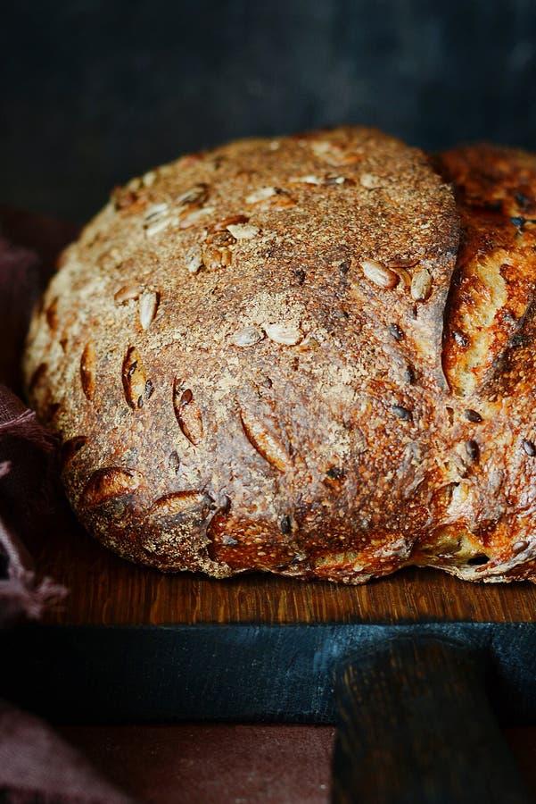 Pan hecho en casa fresco en un fondo oscuro Pan en la harina de centeno con las semillas del lino y del girasol Pan ácimo Tiempo  foto de archivo libre de regalías