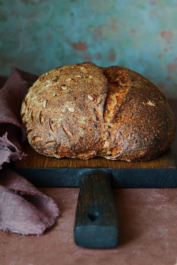 Pan hecho en casa fresco en un fondo oscuro Pan en la harina de centeno con las semillas del lino y del girasol Pan ácimo Tiempo  fotos de archivo libres de regalías