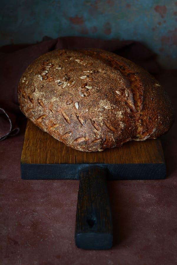 Pan hecho en casa fresco en un fondo oscuro Pan en la harina de centeno con las semillas del lino y del girasol Pan ácimo Tiempo  fotos de archivo