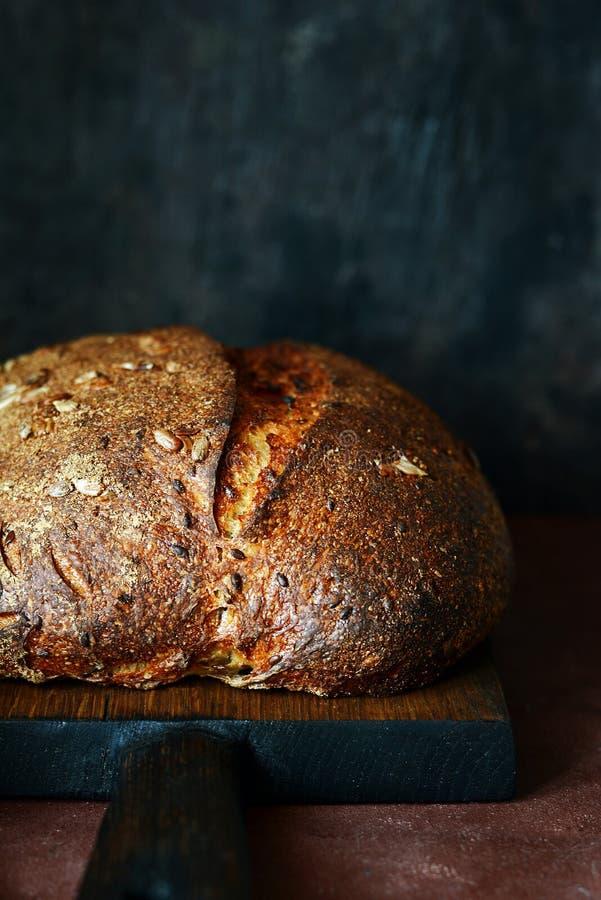 Pan hecho en casa fresco en un fondo oscuro Pan en la harina de centeno con las semillas del lino y del girasol Pan ácimo Tiempo  imagen de archivo libre de regalías