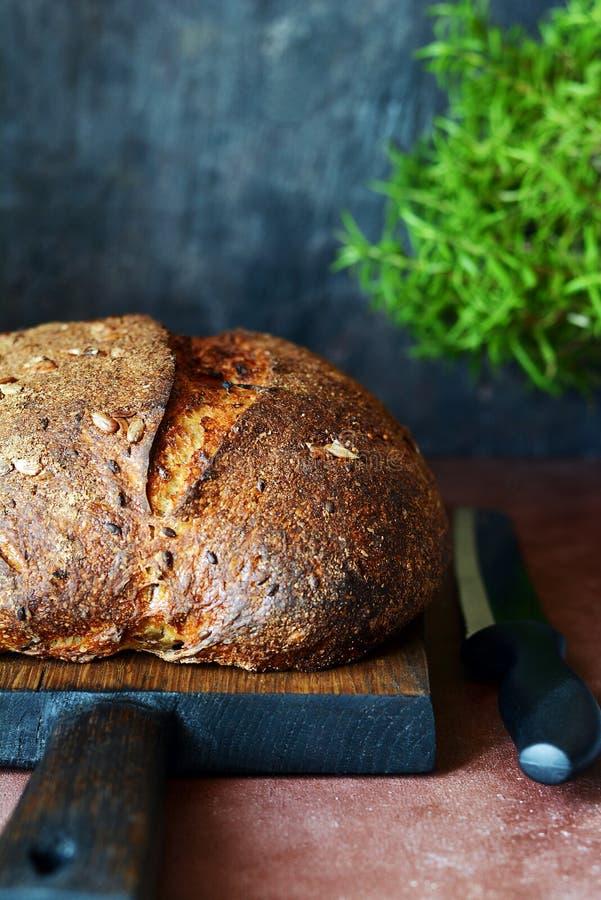Pan hecho en casa fresco en un fondo oscuro Pan en la harina de centeno con las semillas del lino y del girasol Pan ácimo Tiempo  foto de archivo