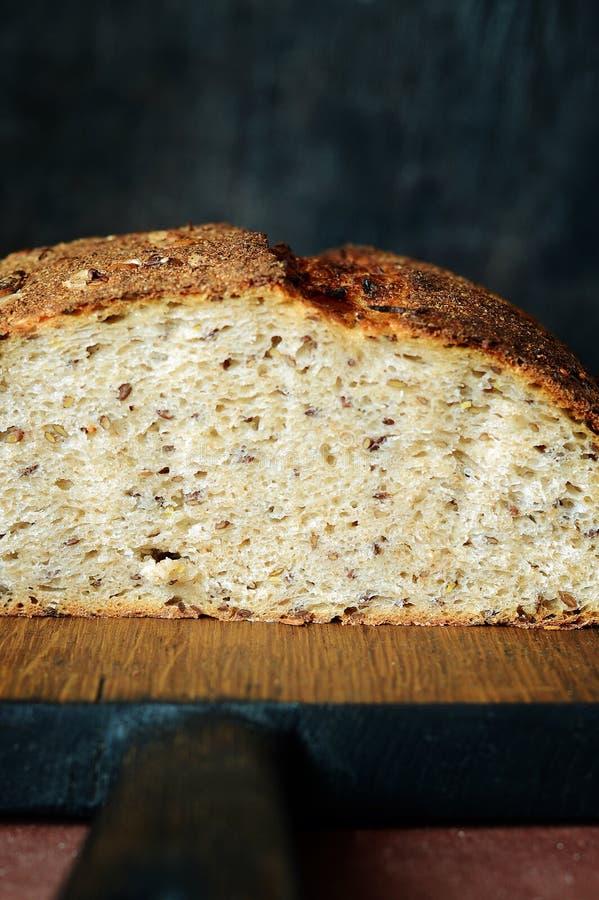 Pan hecho en casa fresco en un fondo oscuro Pan en la harina de centeno con las semillas del lino y del girasol Pan ácimo Tiempo  fotografía de archivo libre de regalías