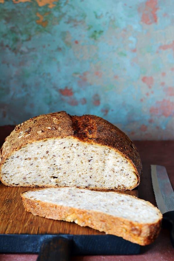Pan hecho en casa fresco en un fondo oscuro Pan en la harina de centeno con las semillas del lino y del girasol Pan ácimo Tiempo  imagen de archivo