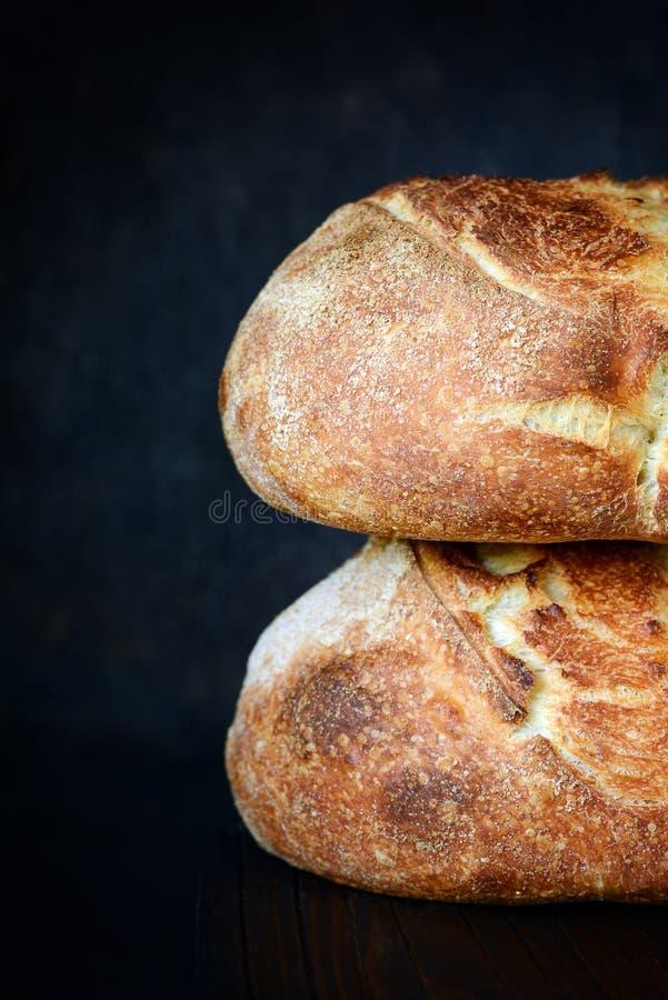 Pan hecho en casa fresco en un fondo oscuro, en la harina del trigo integral Forma redonda del pan francés Hornada del pan ácimo fotos de archivo
