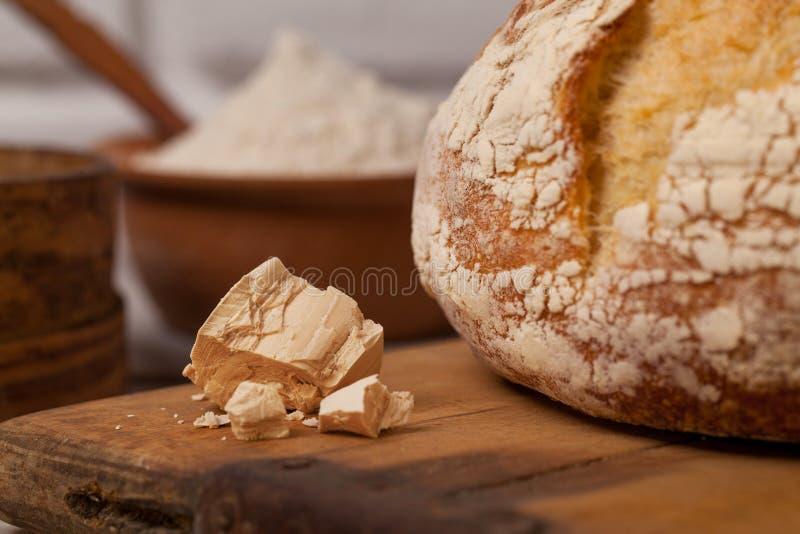 Pan hecho en casa en vieja tabla de cortar con una pila de levadura fresca imagen de archivo