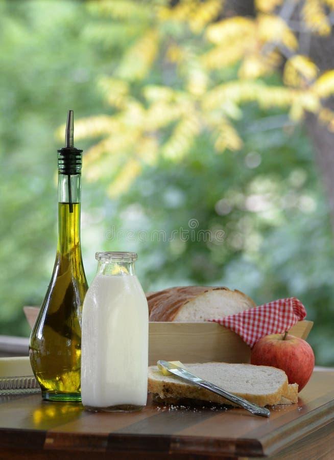 Pan hecho en casa y manzana del aceite de oliva del jarro de leche picinic con estilo al aire libre del vintage imagen de archivo