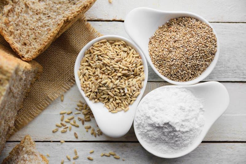 Pan integral en una tela de la arpillera al lado de alguna harina y cereales, desde arriba fotografía de archivo