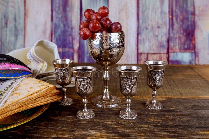 Pan judío del día de fiesta del matzoh de la pascua judía, cuatro vidrios del vino kosher sobre la tabla de madera fotos de archivo libres de regalías