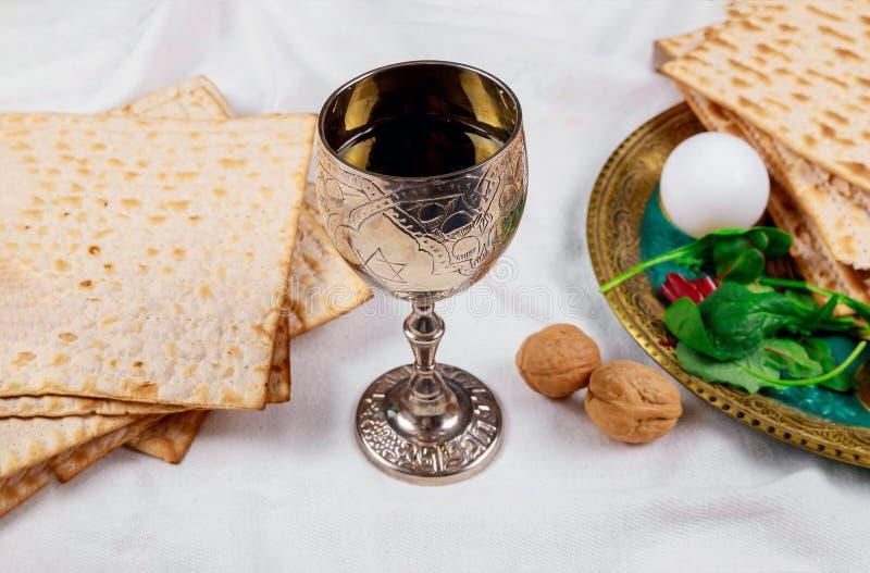 Pan judío del día de fiesta del matzoh de la pascua judía, vino kosher de los vidrios sobre la tabla de madera fotografía de archivo