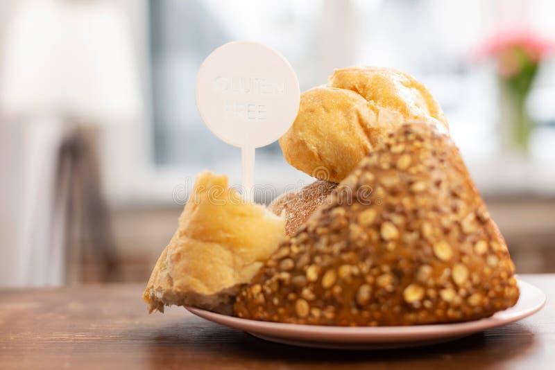 Pan libre y bollos del gluten que se colocan en la tabla de madera fotografía de archivo