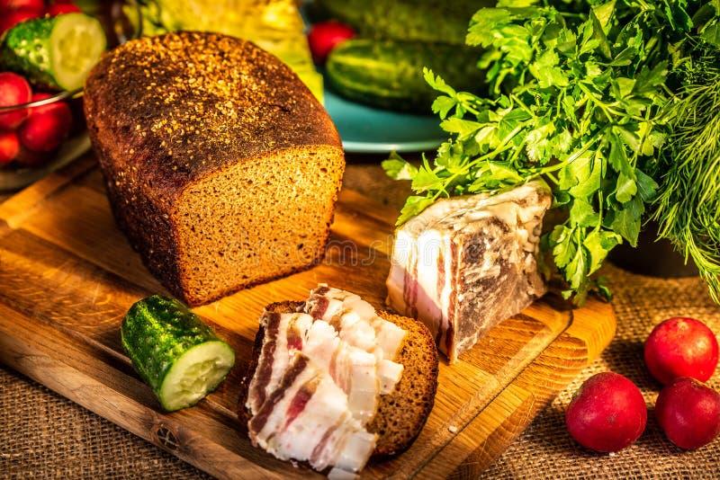 Pan, manteca de cerdo y r?bano de Rye en un tablero de madera en los rayos de la luz del sol fotografía de archivo libre de regalías