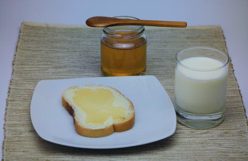 pan, mantequilla, miel y leche imagen de archivo