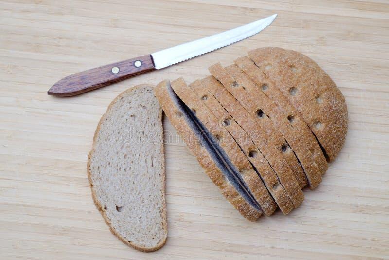 Pan marrón cortado en el escritorio de madera fotografía de archivo
