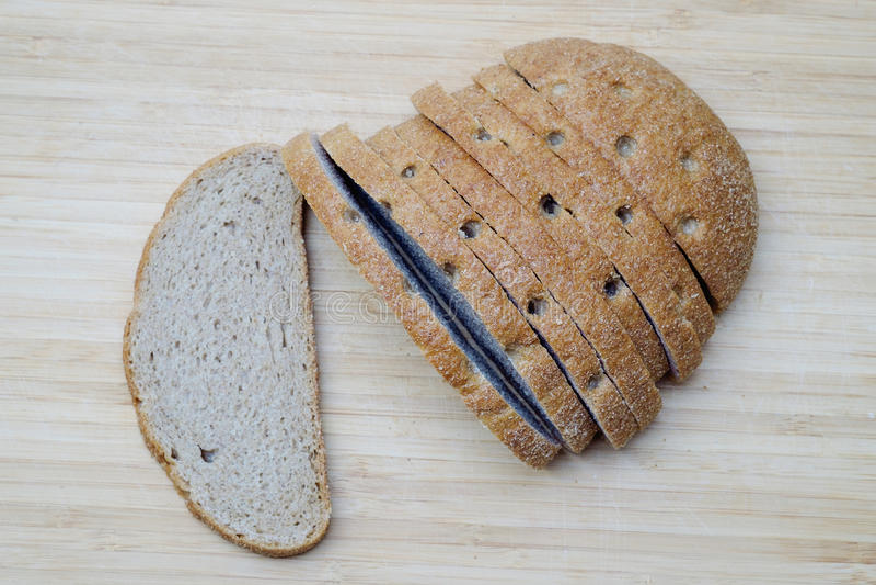 Pan marrón cortado en el escritorio de madera imagen de archivo