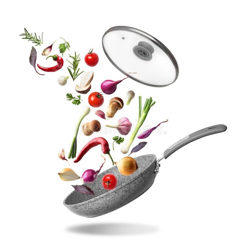 Pan met deksel en vliegende die groenten, op witte achtergrond wordt geïsoleerd stock fotografie
