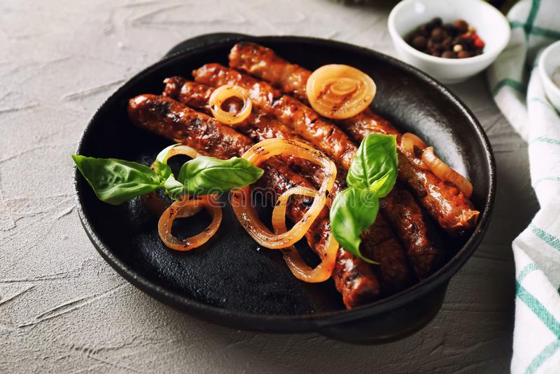 Pan met smakelijke geroosterde worsten en ui op lijst stock foto