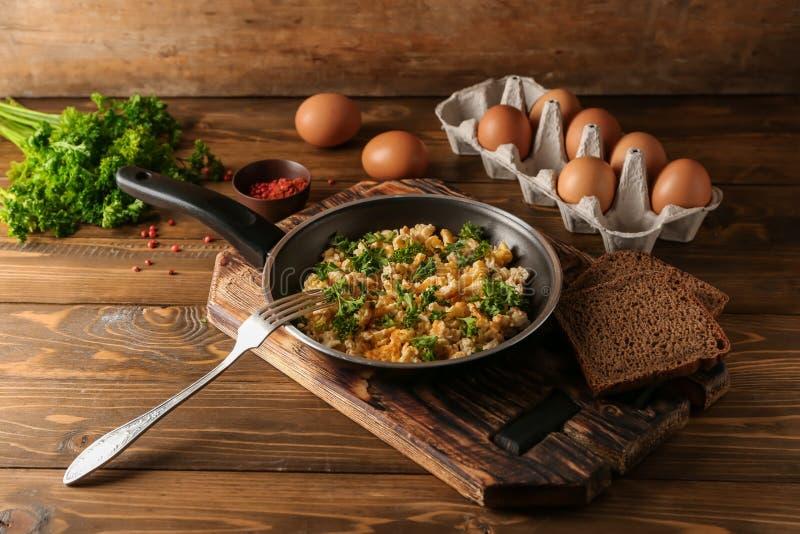 Pan met smakelijke omelet en brood op houten lijst stock foto's