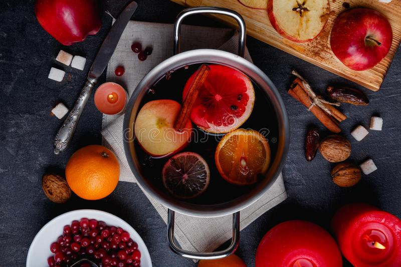 A pan with a mulled wine with orange, lemon, apples and cinnamon. View from above. stock photos