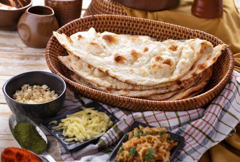 Pan naan indio con algunos ingredientes de la comida india fotografía de archivo