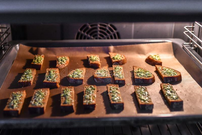 Pan negro con queso en el horno Pan asado con el queso y las especias, cocinados en el horno en una bandeja negra, desayuno delic imagen de archivo