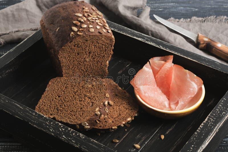 Pan negro y tocino en una bandeja de madera foto de archivo libre de regalías