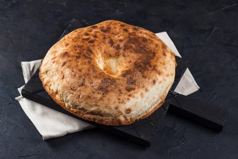 Pan Pita armenio redondo en un tablero y servilleta en un fondo oscuro fotos de archivo