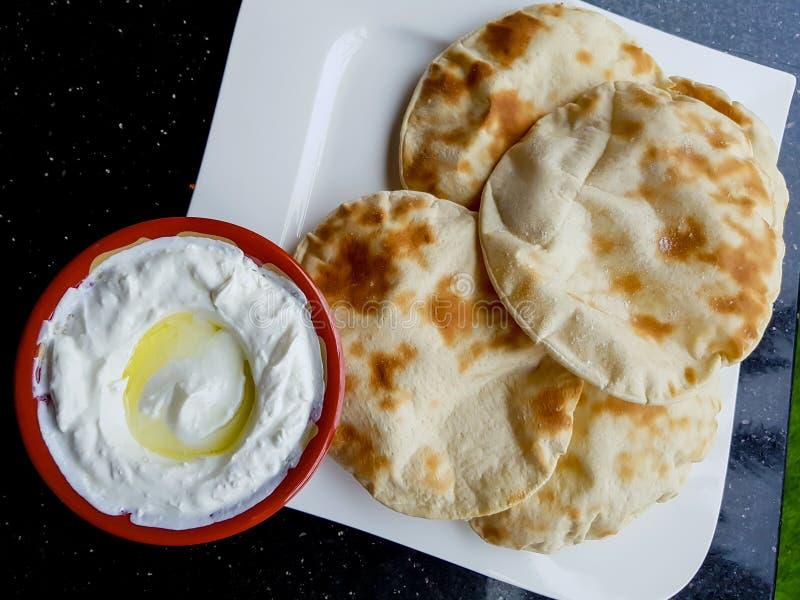 Pan plano de Labneh y del pitta, visto desde arriba Inmersión de queso cremoso libanesa del yogur, servida con aceite de oliva imagen de archivo