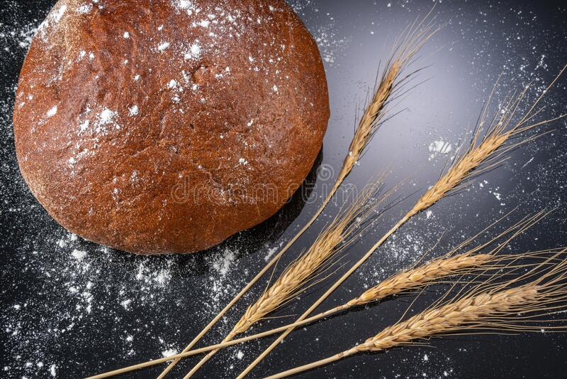 Pan quemado y orejas de trigo fotografía de archivo