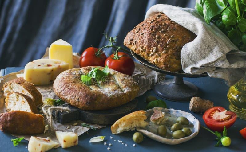 Pan, queso y tomates del grano en fondo azul fotografía de archivo