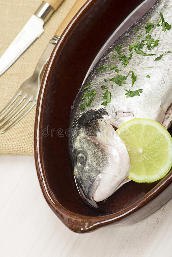 A pan with raw fish standing near fork and knife. Vertical studio shot. Food stock photography