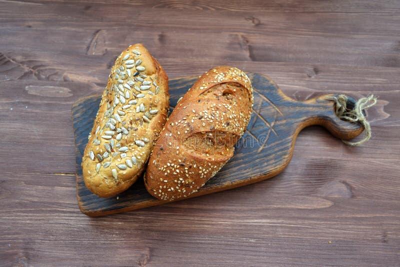 Pan recientemente cocido de la harina de trigo con las semillas de girasol, calabaza, endecha del plano del sésamo en tablero coo fotos de archivo libres de regalías