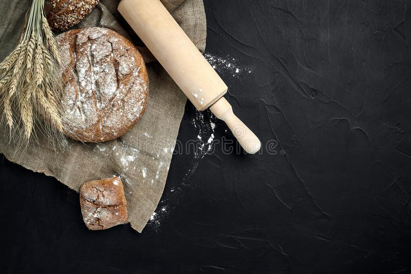 Pan recientemente cocido en la tabla de cocina oscura, visión superior fotografía de archivo
