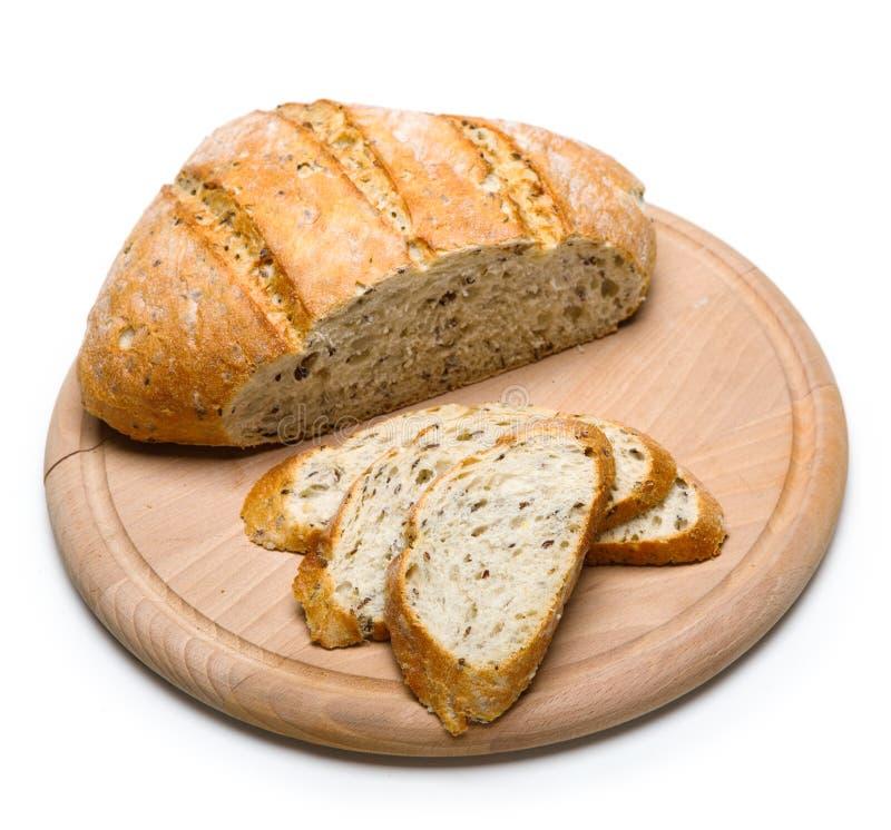 Pan recientemente cocido en la tabla de cortar de madera aislada en el fondo blanco imagen de archivo libre de regalías