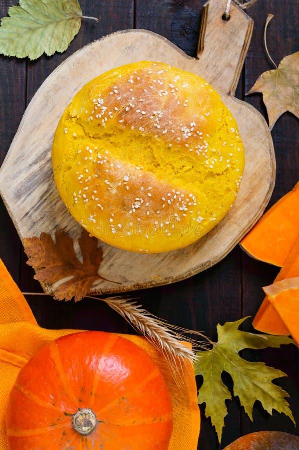 Pan recientemente cocido hecho en casa de oro de la calabaza con las semillas de sésamo en un fondo de madera oscuro imagen de archivo
