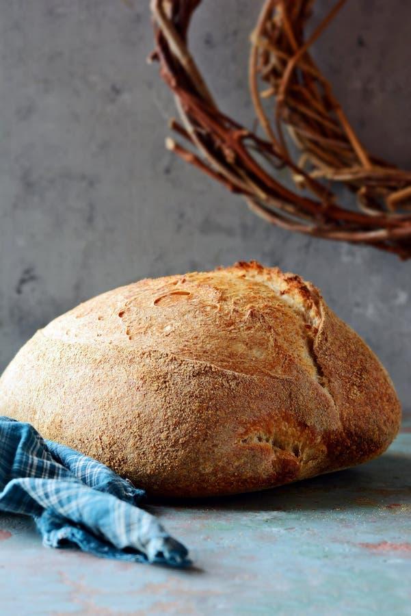 Pan recientemente cocido hecho en casa del país hecho de trigo y de harina entera del grano en un fondo gris-azul imagen de archivo libre de regalías