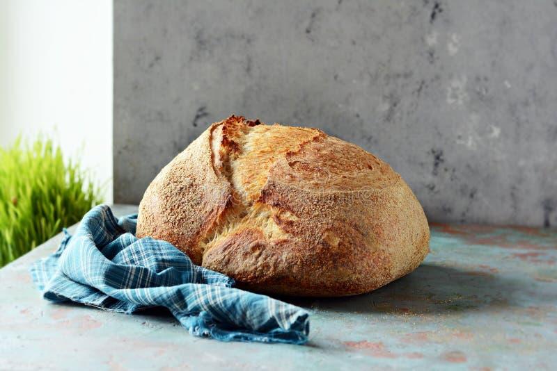 Pan recientemente cocido hecho en casa del país hecho de trigo y de harina entera del grano en un fondo gris-azul fotos de archivo libres de regalías