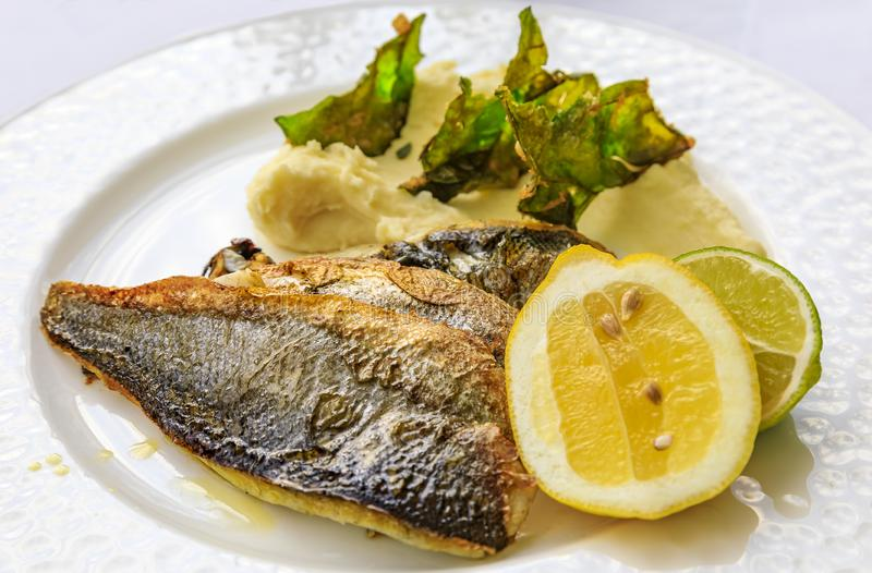 Pan seared branzino or sea bass with mashed potatoes and deep fried kale chips at an al fresco restaurant in Montenegro royalty free stock image