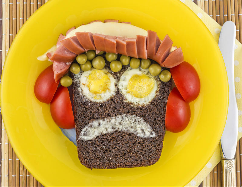 Pan sonriente de la tostada en una placa amarilla foto de archivo