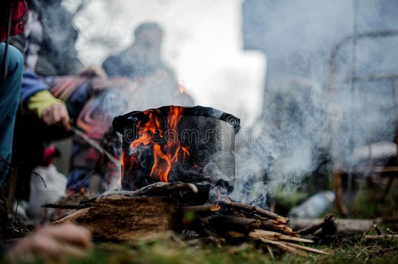 Pan standing on the campfire on the background of the group of people. Pan with a dish standing on the campfire on the background of the group of people stock photography
