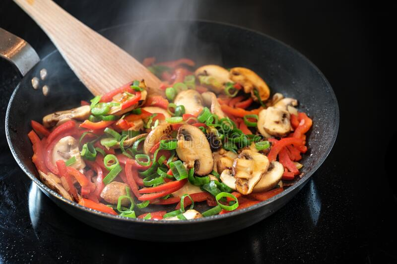 Pan of steaming vegetables with red pepper, mushrooms and spring onion on the black stove, healthy cooking concept, copy space royalty free stock images