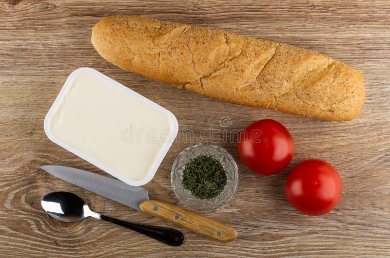 Pan, tarro plástico con el queso cremoso, tomates, cuenco con el eneldo, cuchillo, cuchara en la tabla de madera Visi?n superior imagen de archivo libre de regalías