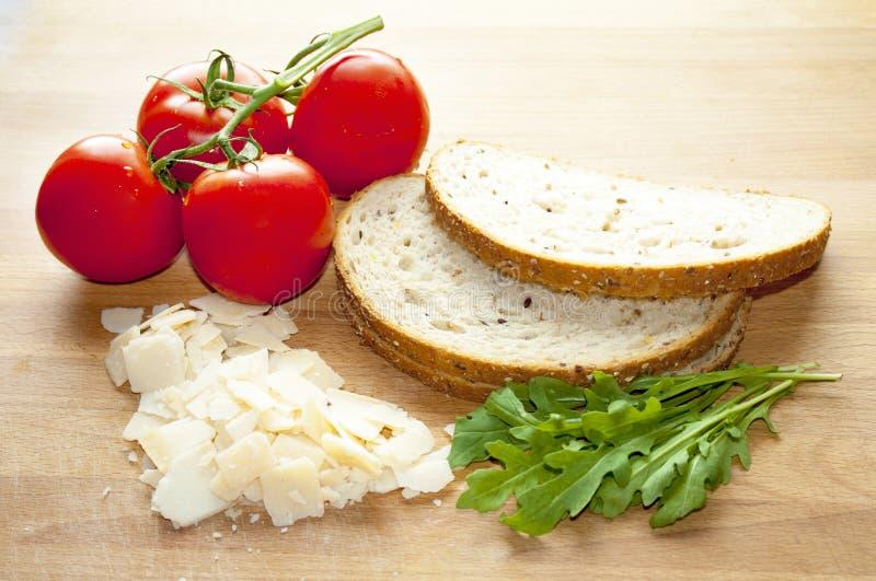Pan, tomates, rukkola y queso del trigo integral fotos de archivo libres de regalías