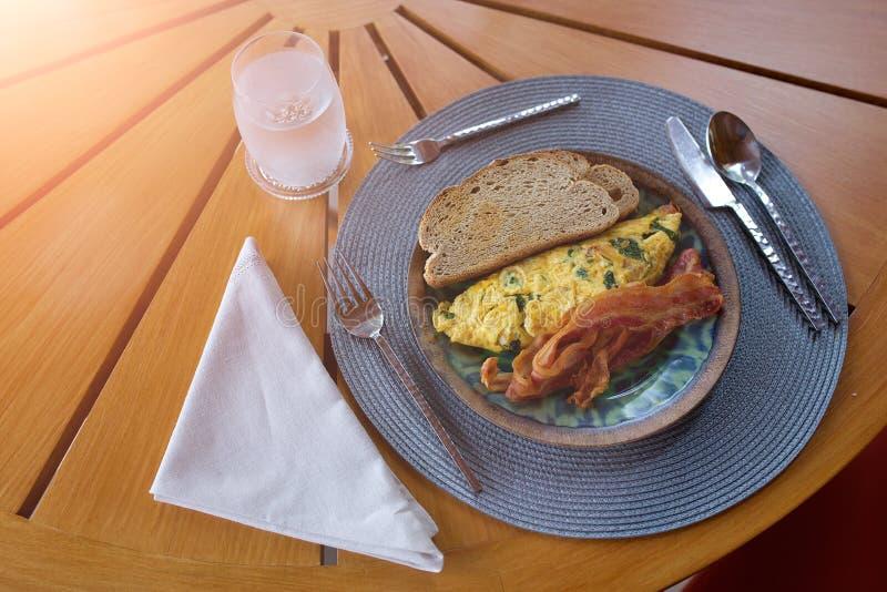 Pan, tortilla y tocino en una placa con el cuchillo y la bifurcación de la cuchara fotografía de archivo